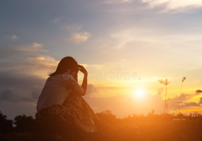 Silhouette of woman praying over beautiful sky background. Silhouette of free cheering woman hiker open arms at mountain peak beautiful sky background royalty free stock photo