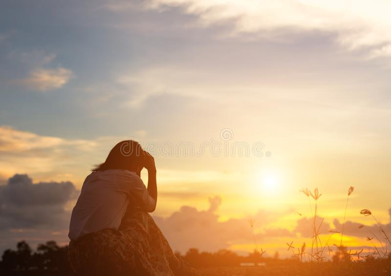 Silhouette of woman praying over beautiful sky background. Silhouette of free cheering woman hiker open arms at mountain peak beautiful sky background royalty free stock image