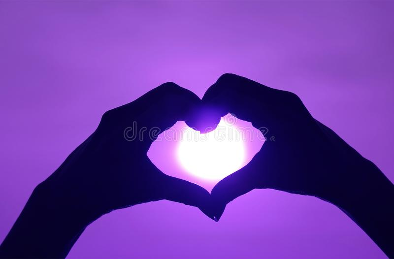 Silhouette of woman`s hand posing LOVE HEART sign against the shiny sun on vibrant purple sky royalty free stock image