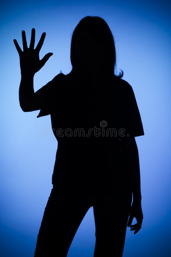 Silhouette of woman showing stop. Isolated on blue silhouette of woman showing stop royalty free stock image