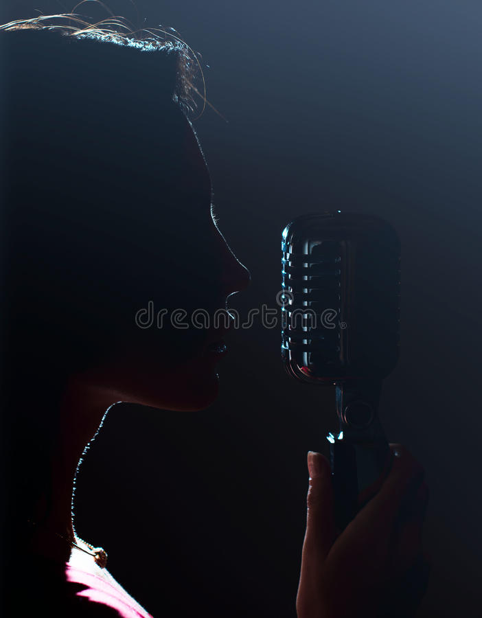 Silhouette of woman singing. Silhouette of woman singing into vintage microphone royalty free stock image