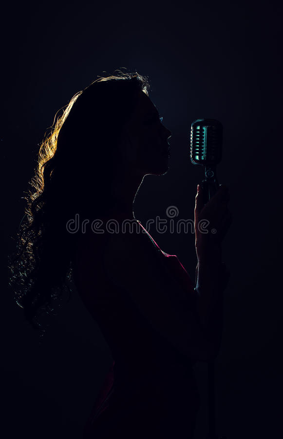 Silhouette of woman singing. Silhouette of woman singing into vintage microphone royalty free stock photos
