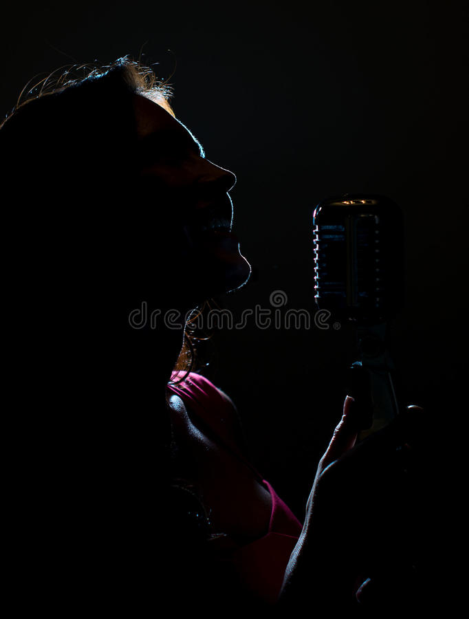 Silhouette of woman singing. Silhouette of woman singing into vintage microphone royalty free stock photo