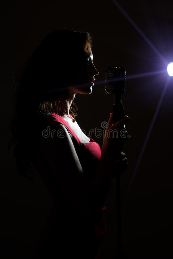 Silhouette of woman singing. Silhouette of woman singing into vintage microphone royalty free stock photography