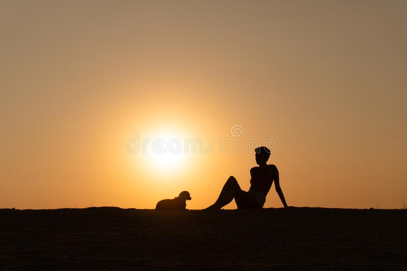 A silhouette of a woman is sitting on the beach stock image