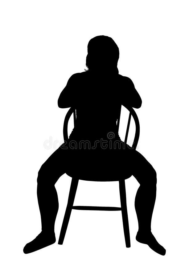 Silhouette of a woman sitting on a chair stock photo