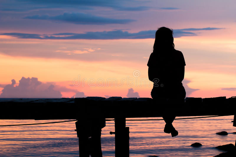 Silhouette woman sitting lonely. stock photo