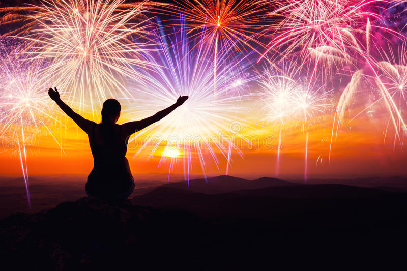 Silhouette of woman sitting and watching the fireworks stock photography