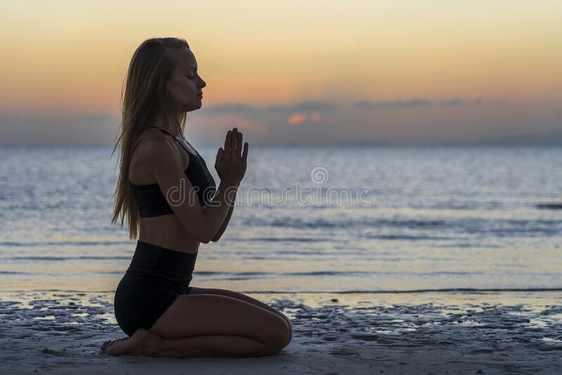 Silhouette of woman sitting at yoga pose on the tropical beach during sunset. Girl practicing yoga near sea water. Silhouette of woman sitting at yoga pose on stock photo
