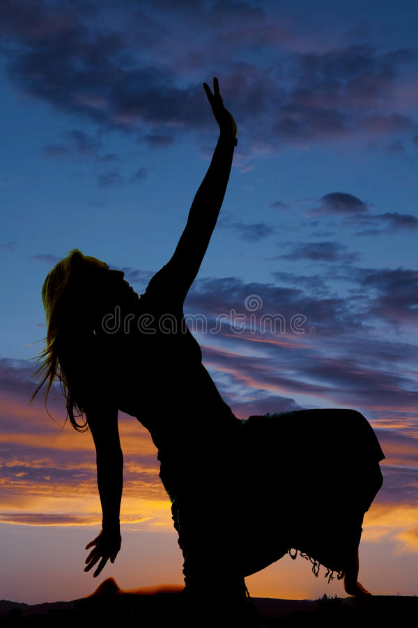 Silhouette of a woman in a skirt kneel hand up stock image