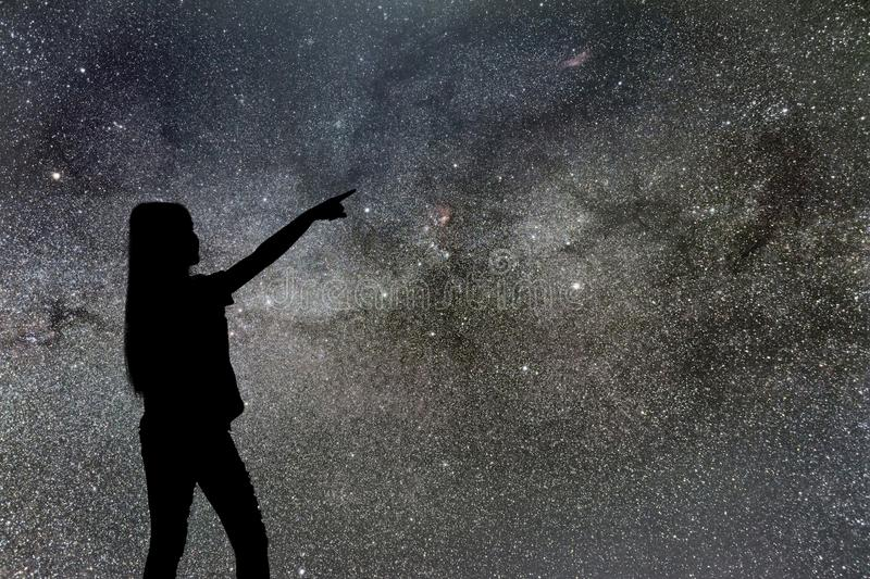 Silhouette of woman stand alone in the night milky way and stars royalty free stock image