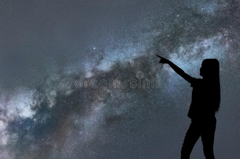 Silhouette of woman stand alone in the night milky way and stars stock images