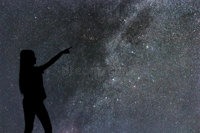 Silhouette of woman stand alone in the night milky way and stars stock image
