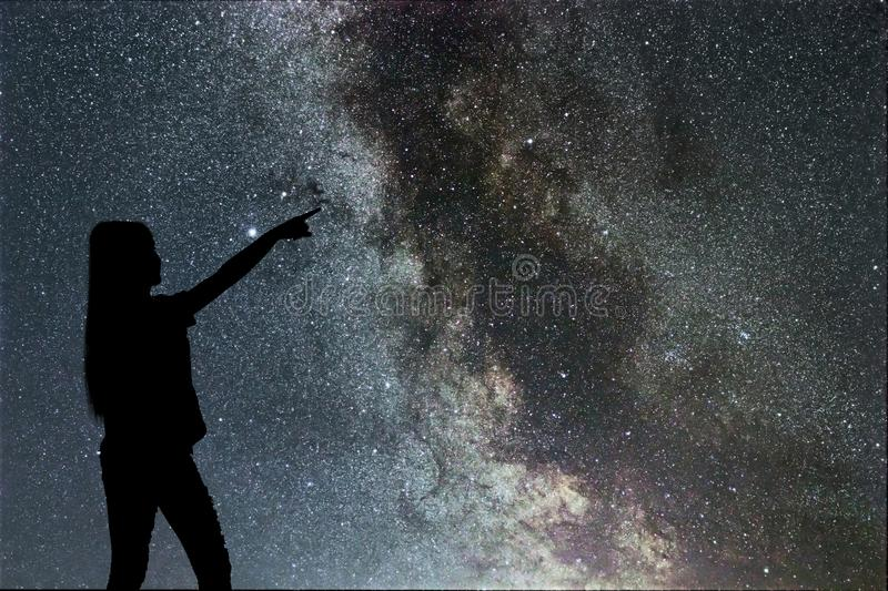 Silhouette of woman stand alone in the night milky way and stars stock photos