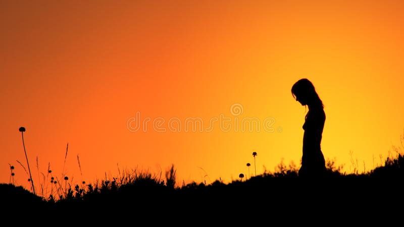 Silhouette Of Woman Standing On Grass Field During Sunset royalty free stock photo