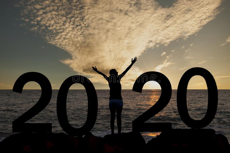 Silhouette of a woman standing in 2020 on the hill at sunrise royalty free stock photography