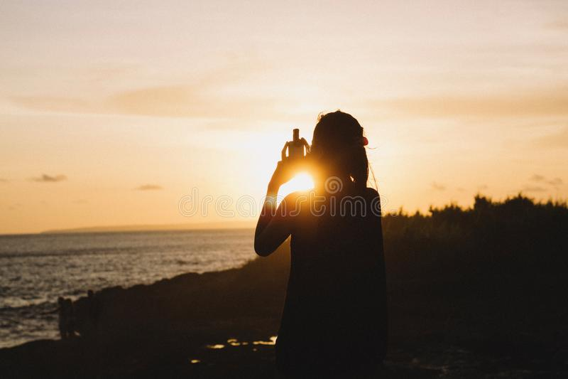 Silhouette of Woman Standing Near Body of Water during Sunset stock photo