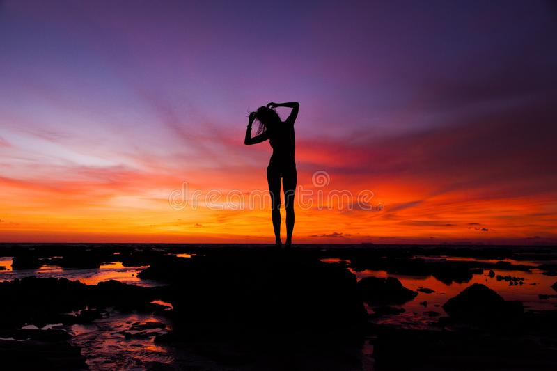 Silhouette of Woman Standing on Rock stock image