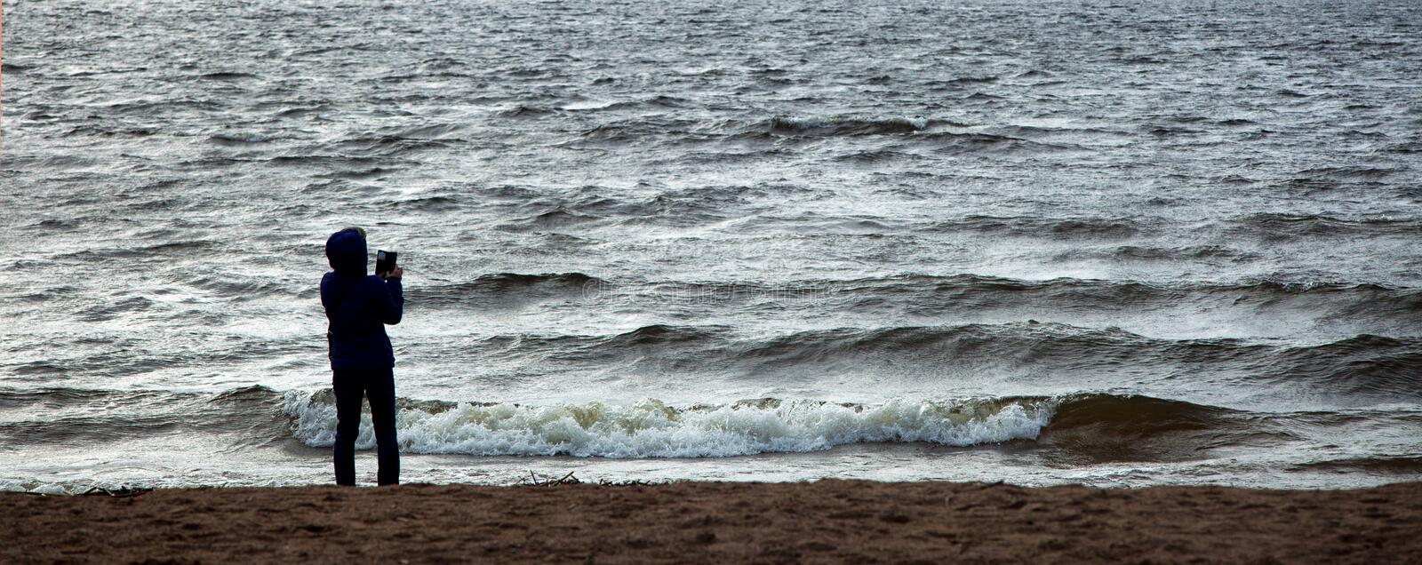 Silhouette of a woman standing on the seashore and taking a photo against the background of the sea waves. Wind. Storm. Panorama stock photos