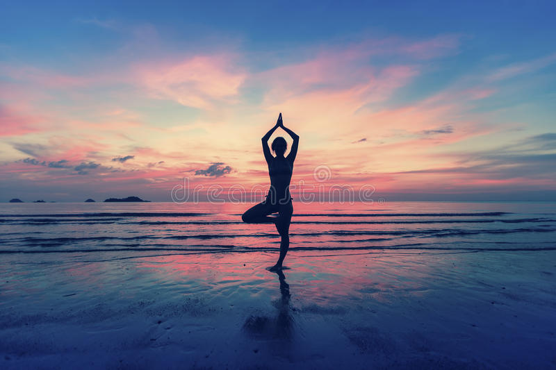 Silhouette of woman standing at yoga pose on the beach royalty free stock images