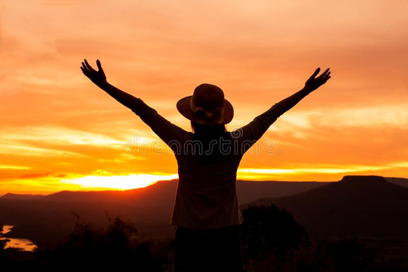 Silhouette woman stands on mountain top at sunset time. Freedom happy woman enjoying nature sunset stock photo