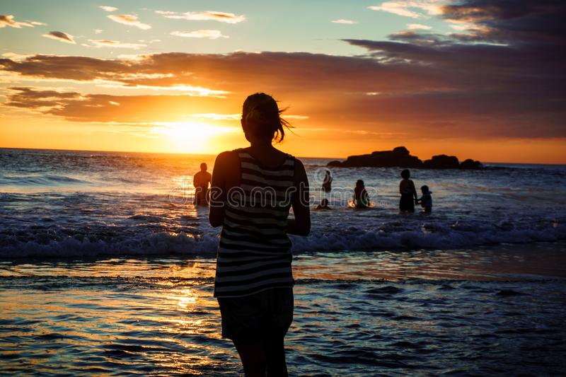 Silhouette of woman on sunset beach, girl walking over sea coast in the summer sunlight royalty free stock photos
