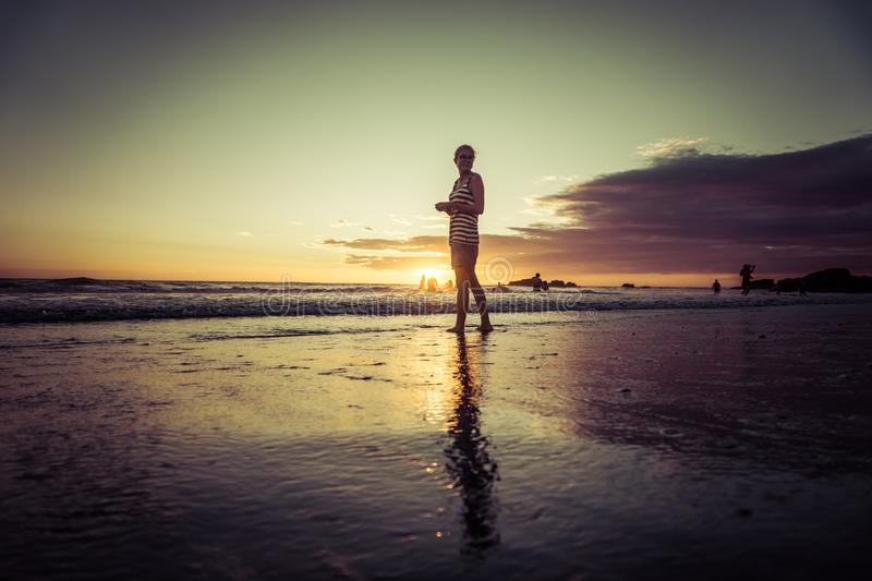 Silhouette of woman on sunset beach, girl walking over sea coast in the summer sunlight royalty free stock images