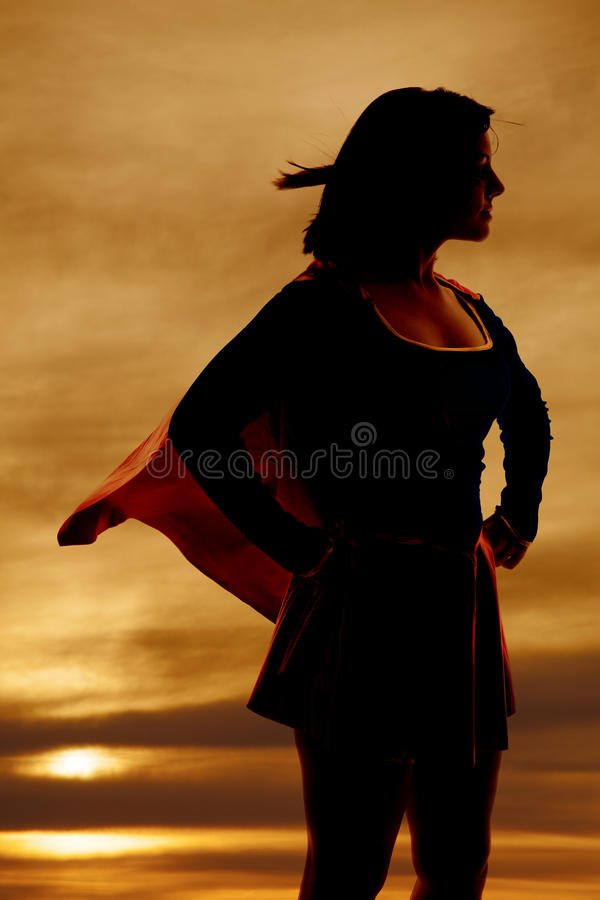 Silhouette woman super hero cape. A silhouette of a woman in her super hero out fit cape flying stock photo