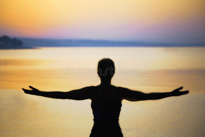Silhouette of woman taking a deep breath at the sunset. In front of the sea royalty free stock image
