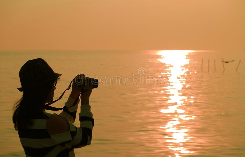 Silhouette of a woman taking pictures at the sun rising seaside. Beauty in Nature royalty free stock image
