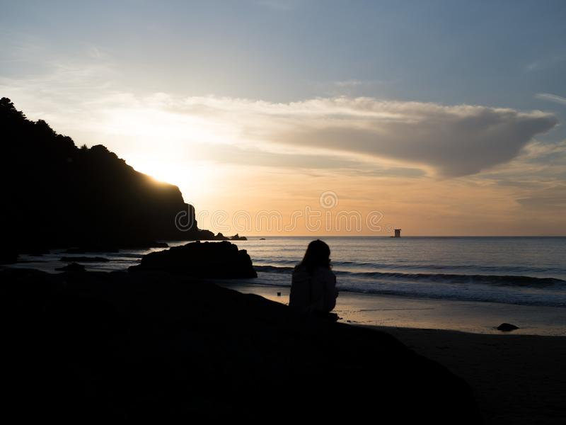 Silhouette of woman taking in sunset at beach stock photo