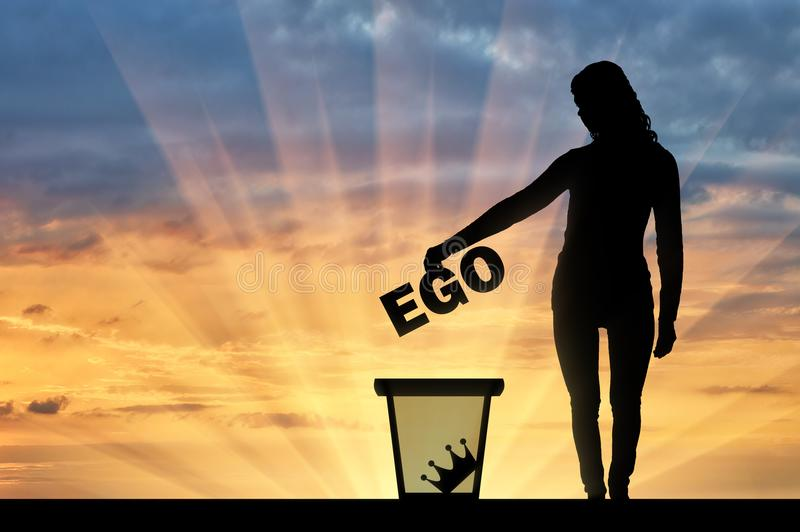 Silhouette of a woman throws the word ego into the garbage bin royalty free stock images