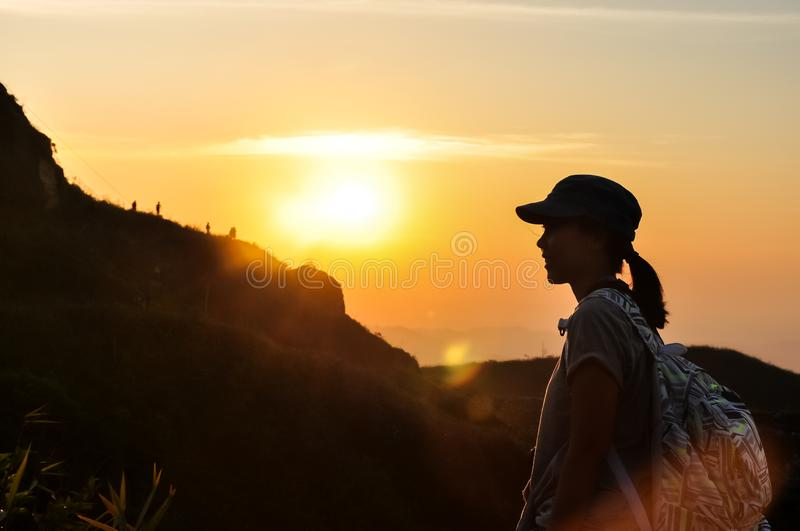 Silhouette woman traveler see view sunset on the mountain in moment of happiness.feel relax lifestyle. Silhouette woman traveler see view sunset on the mountain royalty free stock image