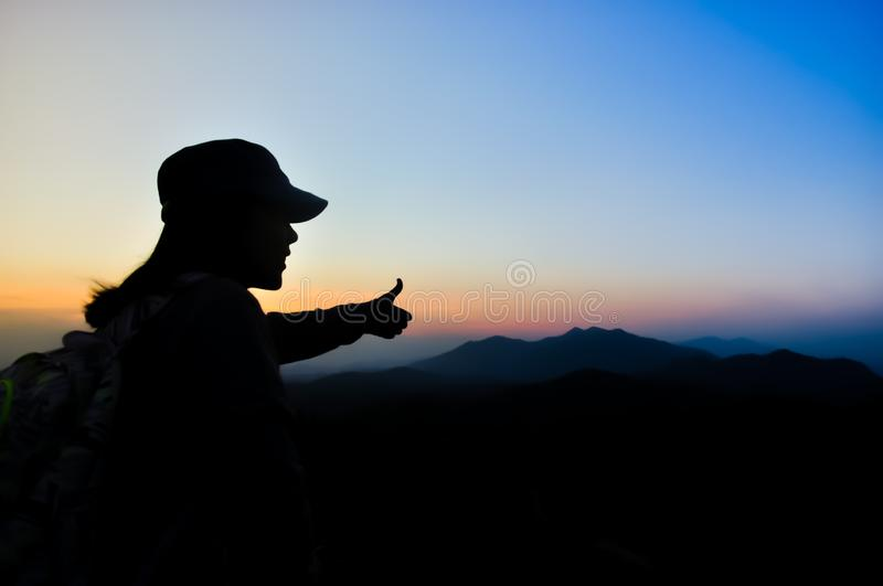 Silhouette woman traveler see view sunset on the mountain in moment of happiness.feel relax lifestyle. Silhouette woman traveler see view sunset on the mountain stock photos
