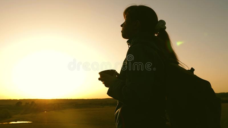 Silhouette woman traveler, stands on top of a hill drinking coffee in glass from thermos. tourist girl drinks hot tea stock images