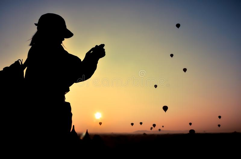 Silhouette woman traveler take photo view sunrise with many hot air balloons above Bagan in Myanmar. royalty free stock photos