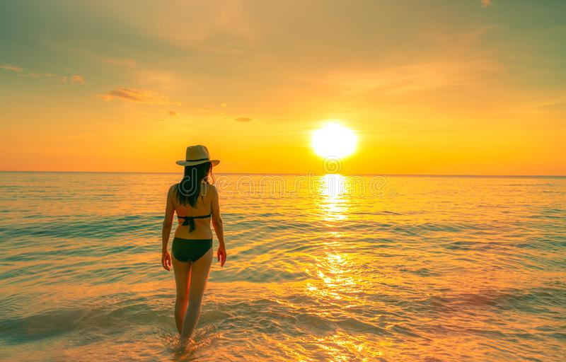 Silhouette woman walking at tropical sea with beautiful sunset sky at paradise beach. Happy girl wear bikini and straw hat re royalty free stock photos