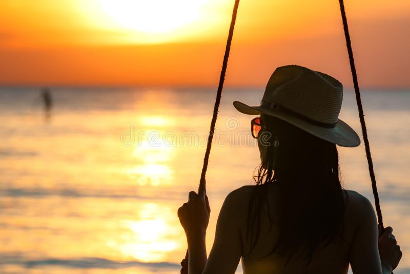 Silhouette woman wear bikini and straw hat swing the swings at the beach on summer vacation at sunset. Girl in swimwear sit royalty free stock image