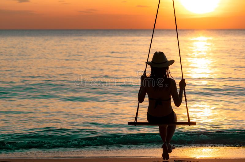 Silhouette woman wear bikini and straw hat swing the swings at the beach on summer vacation at sunset. Girl in swimwear sit royalty free stock photos