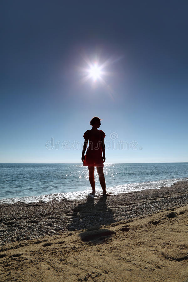 Silhouette of woman which stands on beach in water