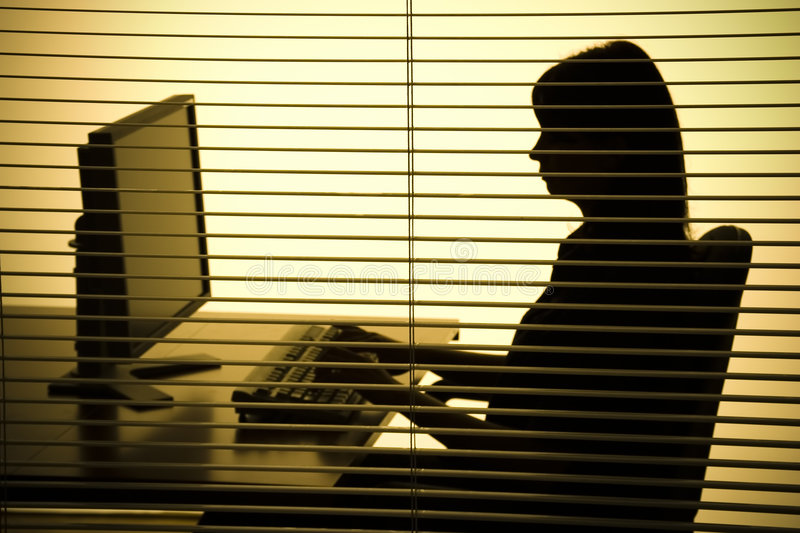 Silhouette of woman working computer (blind) stock image