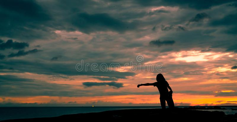 Silhouette woman workout in the morning at stone beach with beautiful sunrise sky. Fit woman runner  stretching body before royalty free stock photography