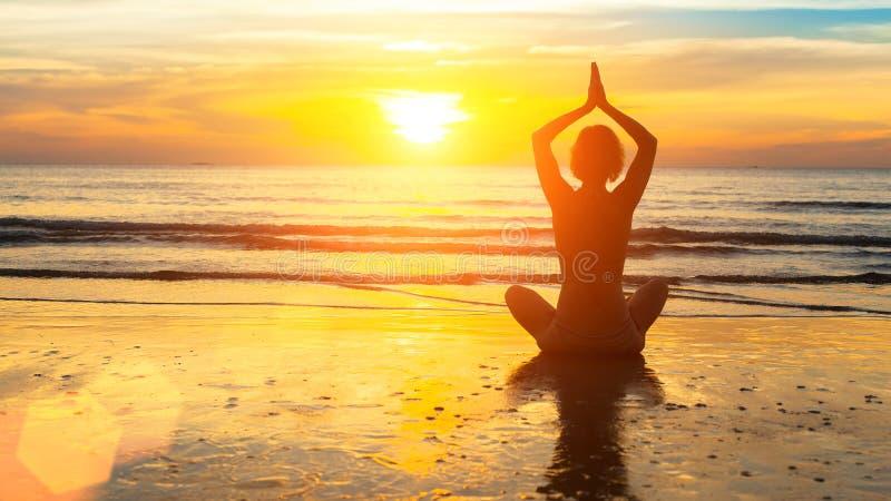 Silhouette woman yoga on the sea beach stock image