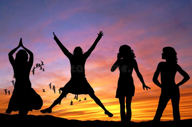 Silhouette of 4 Women With the Background of Birds Flying Under Yellow and Grey Sky stock photos