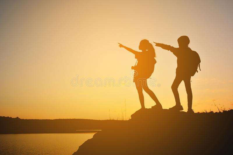 Silhouette women and girl backpacker on the top mountain stock images