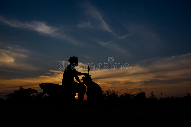 Silhouette of a women sitting on a motorcycle. stock images