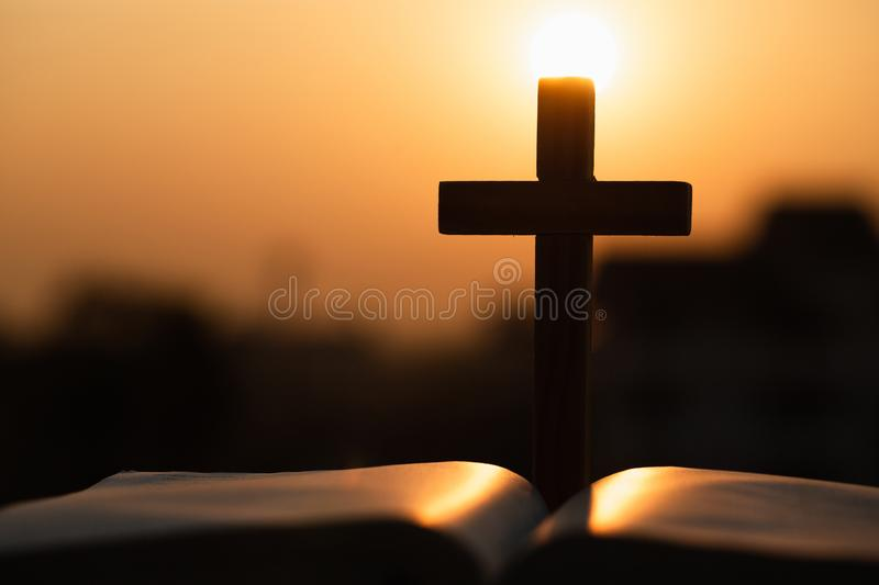 Silhouette of the wooden cross over opened bible with a bright sunrise as background , Christian, god.  royalty free stock photography