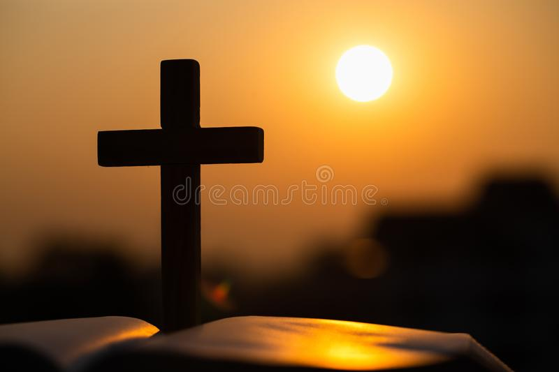 Silhouette of the wooden cross over opened bible with a bright sunrise as background , Christian, god royalty free stock photography