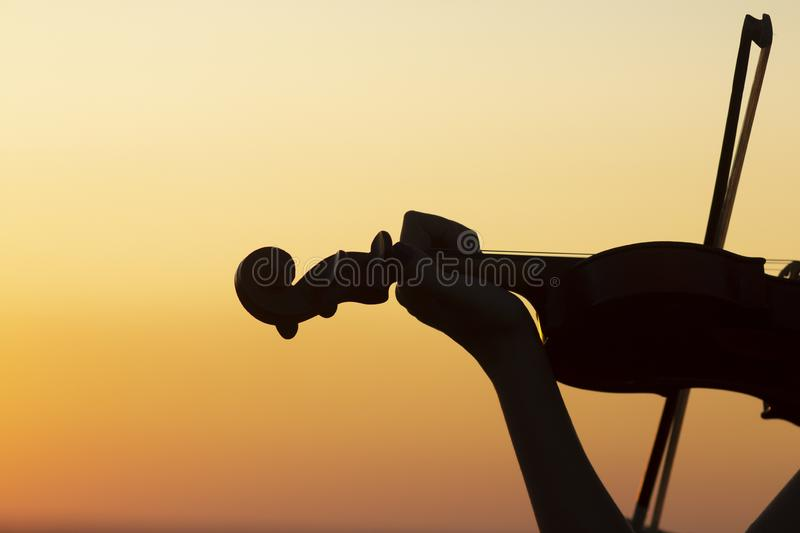 Silhouette of a wooden violin in female hands, the figure of a stringed musical instrument on a sunset sky, the concept of music. And art stock image