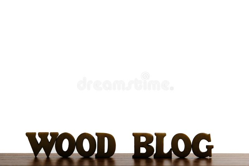 The words WOOD BLOG are made of wooden letters on a background of dark brown wood.Copy space on top for an inscription or logo.. S stock images